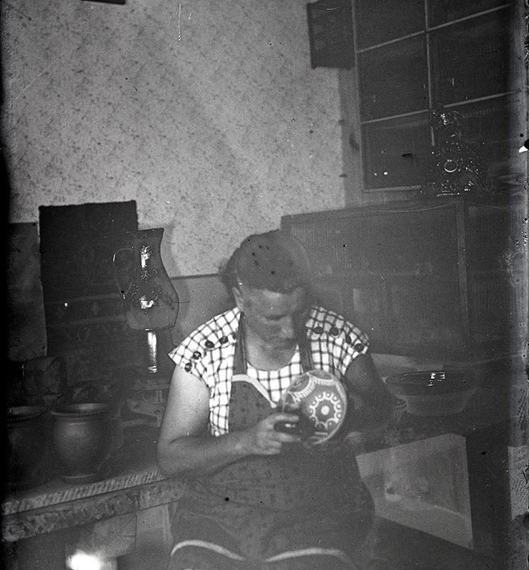 Kobieta w pracowni garncarskiej, ukazana w pozycji siedzącej, do kolan, przy pracy - zdobieniu miseczki. Ubrana jest w jasną sukienkę w kratkę i ciemny fartuch. Mężczyzna we wnętrzu pracowni garncarskiej, wyrabiający gliniane naczynia na kole garncarskim. Ubrany jest w białą koszulę. Na stole stoją gliniane naczynia. W tle ściana pokryta tapetą, na niej z lewej strony, dyplom w ramce.
