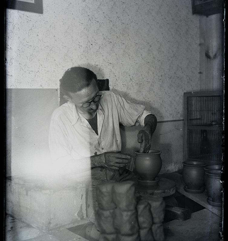 We wnętrzu pracowni garncarskiej mężczyzna w białym fartuchu, stojący za kołem garncarskim i wyrabiający z gliny naczynie. Przed nim na stole, z prawej strony, stoją naczynia gliniane, z lewej glina w prostokątnych kawałkach.