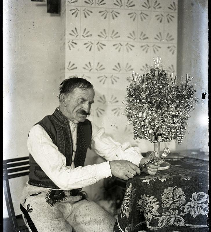 Mężczyzna ukazany przy pracy – zdobieniu rózg weselnych w izbie, w pozycji siedzącej, do kolan. Z prawej strony stół przykryty wzorzystą tkaniną, na którym stoi rózga weselna w kształcie drzewka zdobionego pozłotkiem i szklanymi paciorkami. W tle zwieszona jasna tkanina zdobiona stylizowanym, ciemnym motywem kwiatowym.