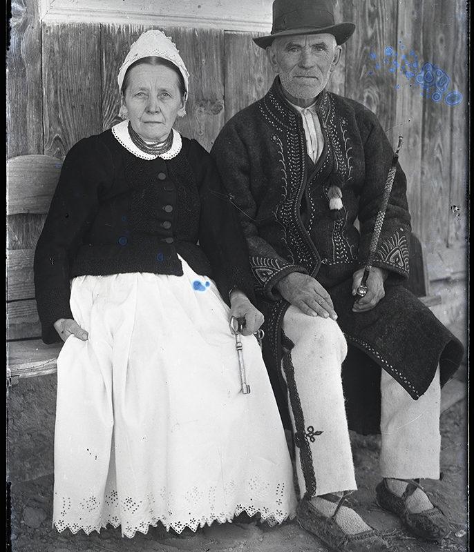 Przedstawia parę starszych ludzi w strojach łąckich, siedzącą na ławce pod ścianą domu. Kobieta ubrana jest w białą, obszerną spódnicę oraz ciemny kubrak zapinany na guziki, na głowie ma biały stożkowaty czepek, w rękach trzyma duże klucze. Mężczyzna ubrany jest w jasne, bawełniane spodnie i ciemną sukmanę zdobioną geometrycznym haftem, na głowie ma kapelusz z wysoką główką, w lewej dłoni trzyma długą fajkę.