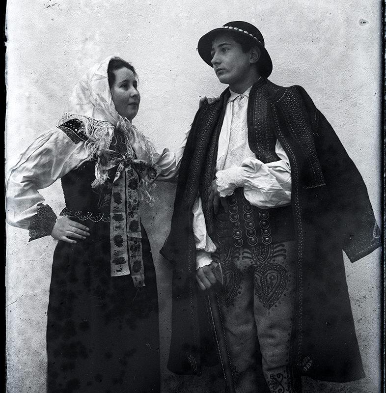 Para młodych ludzi w strojach górali łąckich. Kobieta stojąca z lewej strony, ubrana jest w ciemną spódnicę i ciemny gorset z przypiętą z przodu kokardą, pod nim nosi białą koszulę z bogato zdobionymi haftem mankietami. Na głowie ma chustkę z frędzlami zawiązaną pod brodą. Mężczyzna ubrany jest w jasne spodnie - portki zdobione geometrycznym haftem i w białą koszulę przepasaną skórzanym pasem oraz ciemną kamizelkę i ciemną sukmanę. Głowa nakryta czarnym kapeluszem o okrągłym rondzie.