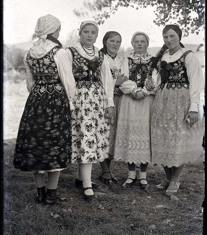 Przedstawia pięć młodych kobiet w strojach łąckich i podhalańskich. Kobieta, z lewej strony, odwrócona do widza plecami, pozostałe cztery ukazane frontalnie. Ubrane w białe bluzki i bogato zdobione haftem koralikowym gorsety oraz w długie spódnice. Dwie kobiety stojące z lewej strony noszą spódnice w drobne kwiatowe motywy, trzy pozostałe koronkowe. Głowy nakryte chustkami zawiązanymi z tyłu.