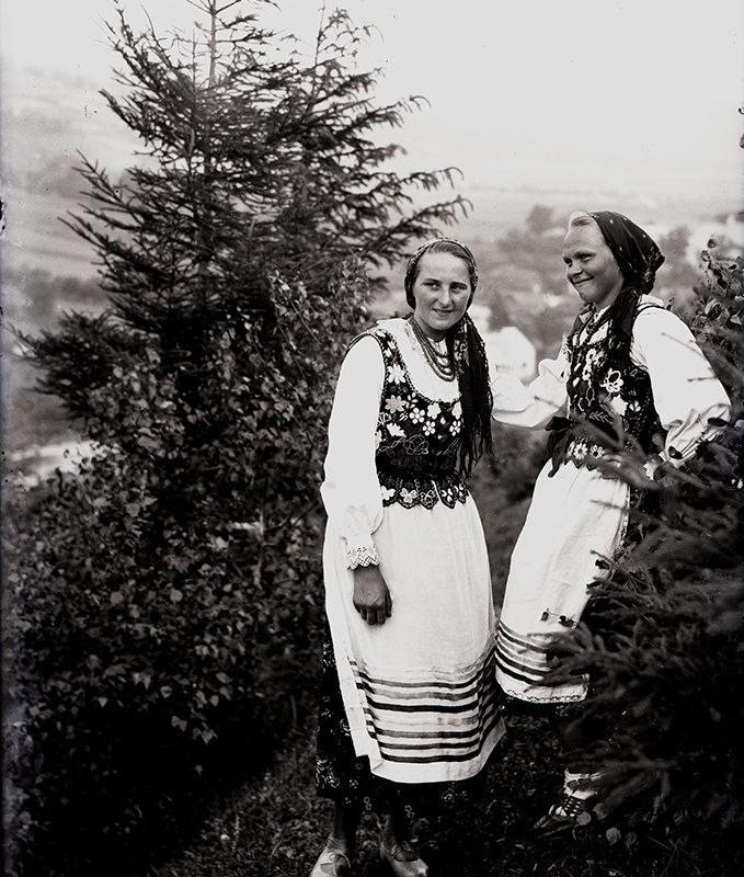 Dwie młode kobiety w strojach góralek łąckich, stojące w otoczeniu świerków. Kobiety ubrane są w białe spódnice z przyszytymi u dołu poprzecznymi wąskimi wstążkami ciemniejszymi i jaśniejszymi oraz białe koszule i ciemne gorsety zdobione haftem o motywie kwiatowym. Na szyi zawieszone sznury korali. Głowy nakryte chustami z frędzlami, zawiązanymi z tyłu.