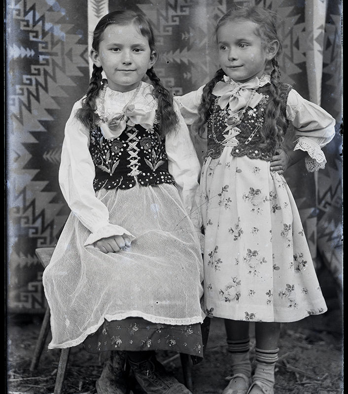 Dwie dziewczynki w strojach góralek łąckich na tle tkaniny w geometryczne motywy. Dziewczynka, z lewej strony starsza, siedzi na krześle i jest ubrana we wzorzystą spódnicę, tiulowy fartuch oraz białą koszulę, na nią ma nałożony gorset zdobiony haftem o motywach kwiatowych. Dziewczynka, z prawej strony, w pozycji stojącej, ubrana jest w jasną spódnicę w kwiatowe motywy, białą koszulę i czarny gorset zdobiony haftem.