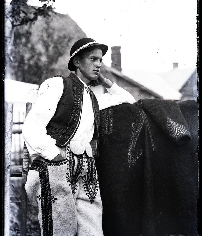 Młody góral opierający się o drewniany płot ubrany w jasne zdobne spodnie, białą koszulę, ciemną haftowaną kamizelkę i kapelusz ozdobiony muszelkami. Przez płot przewieszona ciemna sukmana - strój Górali Łąckich (biały kamieniecki)