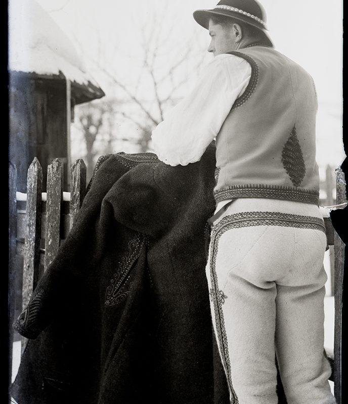 Góral stojący przy drewnianym płocie w spodniach i w kamizelce z motywem paproci na plecach, przez płot przewieszona ciemna sukmana – strój Górali Łąckich (czarny - kamieniecki)