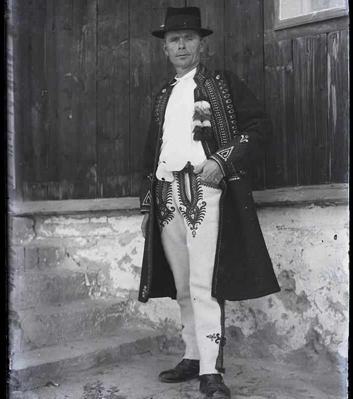 Góral stojący przed drewnianą chałupą z podmurówką w jasnych, ozdobnych spodniach, białej koszuli, ciemnej, haftowanej sukmanie oraz w kapeluszu