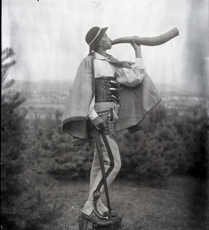 Stojący bokiem na polanie, na pieńku góral w stroju podhalańskim gra na rogu. Mężczyzna ubrany jest w zdobne spodnie, białą koszule, skórzany, szeroki pas, pelerynę i kapelusz ozdobiony muszelkami