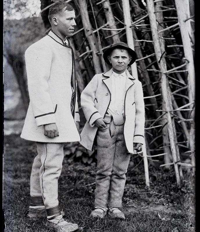 Młody mężczyzna i nastolatek w strojach Górali Sądeckich. Ubrani są w jasne spodnie, koszule i kaftany, nastolatek ma na głowie kapelusz.