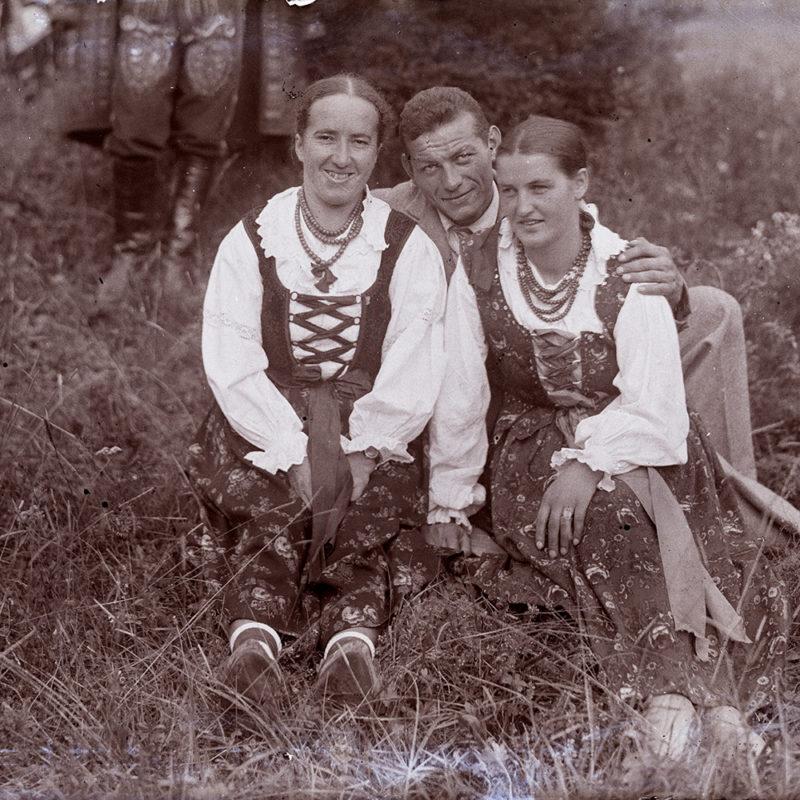 Na polanie siedzą dwie góralki w strojach podhalańskich oraz mężczyzna w garniturze