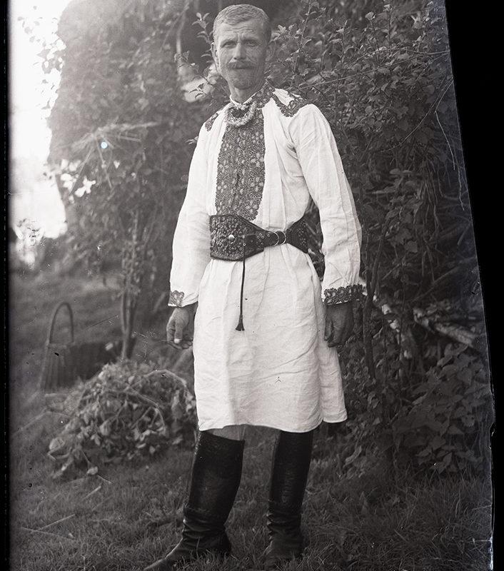 Gazda Podegrodzki w stroju Lachów Sądeckich ubrany w długą do kolan koszulę, haftowaną przy gorsie i mankietach, przepasany zdobnym, skórzanym pasem