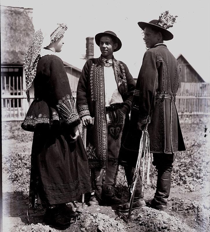 Kobieta i dwóch mężczyzn w strojach weselnych Lachów Sądeckich. Kobieta w spódnicy, kaftanie z baskinką i haftowanymi mankietami oraz w chuście na głowie. Mężczyźni ubrani w zdobne spodnie, białe koszule, haftowane sukmany i kapelusze