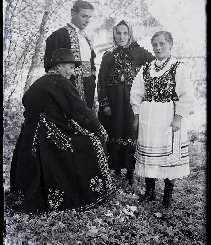 Grupa czterech osób. Starsza kobieta w spódnicy oraz haftowanej kurtce na ramionach, na głowie ma haftowaną chustę, młodsza kobieta w spódnicy, w białej haftowanej bluzce oraz bogato haftowanym gorsecie, z koralami na szyi. Starszy siedzący bokiem mężczyzna w w haftowanym okryciu wierzchnim oraz w kapeluszu, młodszy w spodniach, bogato haftowanym okryciu wierzchnim oraz z szerokim skórzanym pasem – strój Lachów Sądeckich
