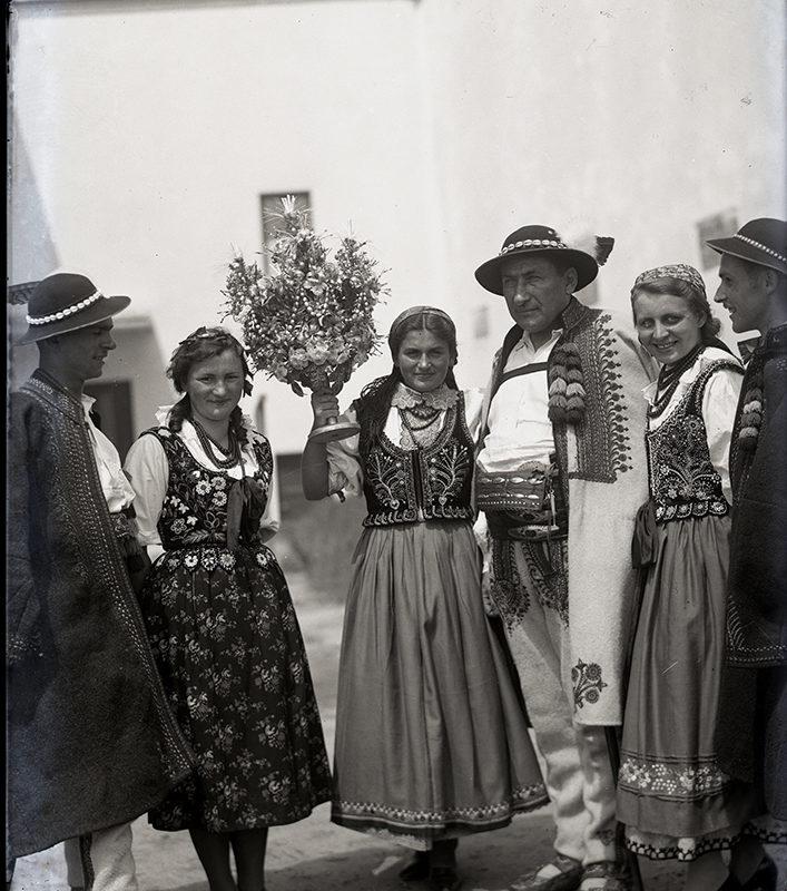 Grupa trzech kobiet i trzech mężczyzn w strojach łąckich z rózgą weselną