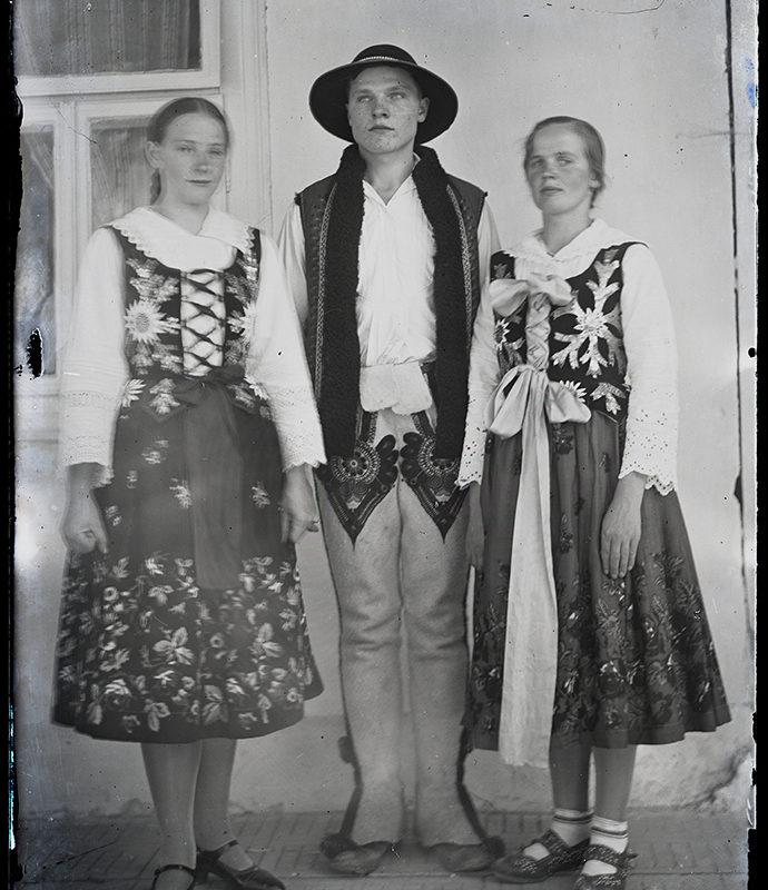 Grupa trzech osób w strojach Górali Podhalańskich. Dwie dziewczyny ubrane w spódnice we wzór kwiatowy, w białe bluzki haftowane przy mankietach i kołnierzyku, w haftowane gorsety. Chłopak ubrany w zdobione spodnie, białą koszulę, kamizelkę i kapelusz