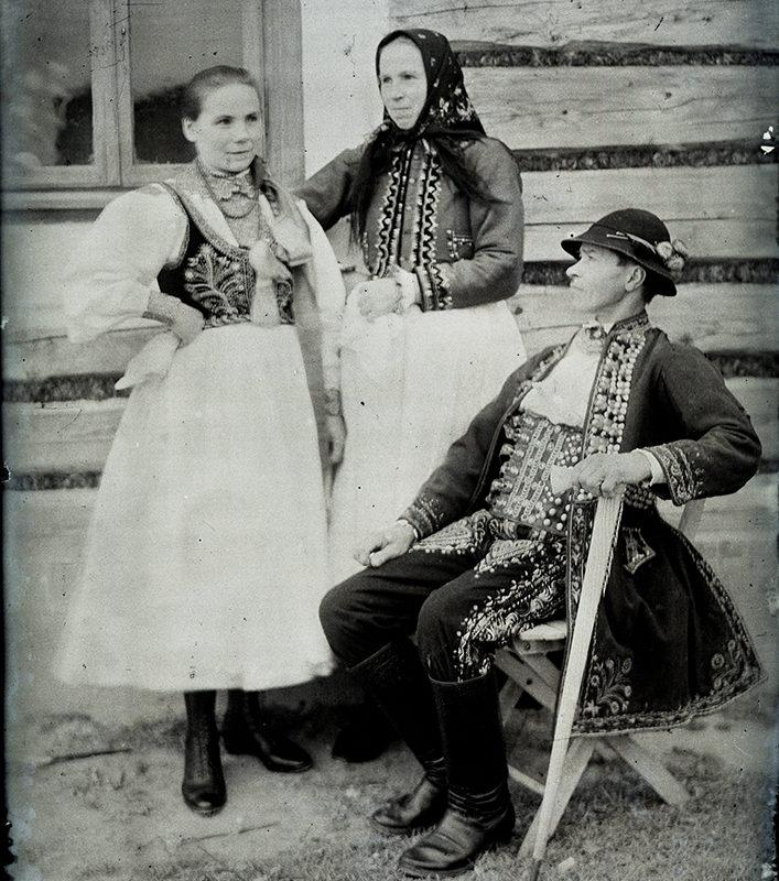 Grupa składająca się z dwóch kobiet i mężczyzny. Młodsza kobieta ubrana jest w białą spódnicę, haftowany gorset i korale, starsza kobieta ma na sobie spódnicę, haftowaną kurtkę i chustę na głowie. Siedzący mężczyzna ubrany jest w haftowane spodnie, bogato haftowane okrycie wierzchnie, skórzany, szeroki pas, kapelusz i podpiera się ciupagą - strój Lachów Sądeckich