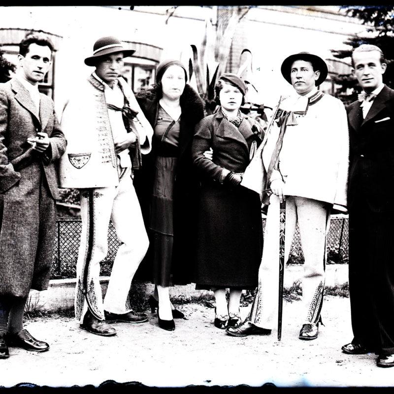 Grupa dwóch kobiet i czterech mężczyzn stojących na ulicy. Dwóch mężczyzn ubranych jest w stroje podhalańskie, dwie kobiety i dwóch pozostałych mężczyzn ubranych jest w stroje miejskie z lat 30. XX w