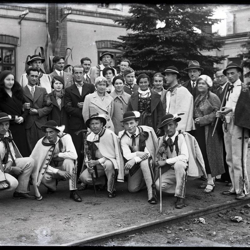 Grupa dwudziestu siedmiu mężczyzn i kobiet w strojach podhalańskich oraz miejskich z lat 30. XX w. Grupa stoi w trzech rzędach. Pierwszy rząd to pięciu klęczących mężczyźni w strojach podhalańskich. Pozostałe osoby stoją w dwóch rzędach
