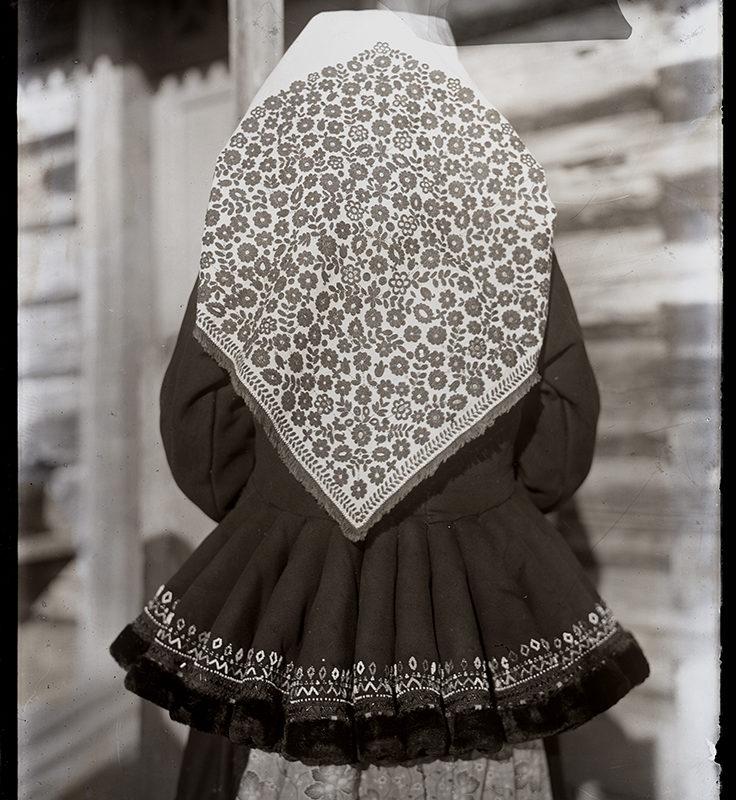 Kobieta stojąca tyłem w chuście i zimowej katanie z baskinką – strój Lachów Sądeckich