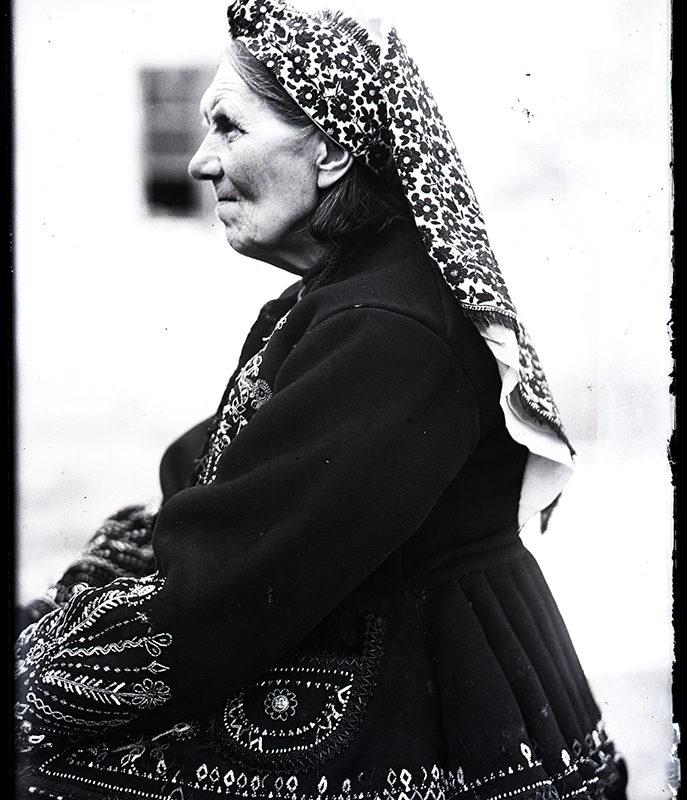 Starsza kobieta siedząca bokiem w chuście i haftowanej katanie zimowej – strój Lachów Sądeckich