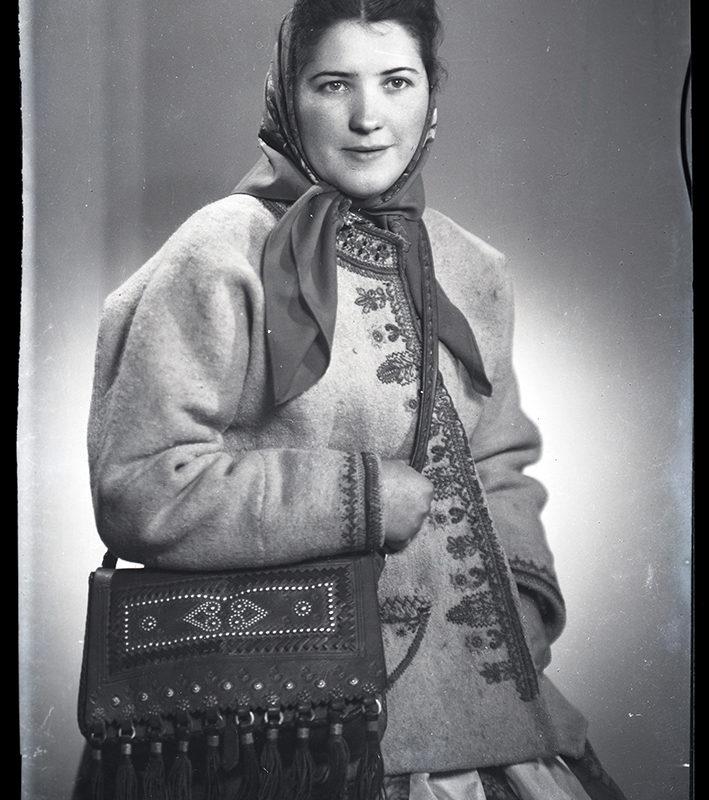 Zdjęcie zrobione w zakładzie fotograficznym. Kobieta ubrana w spódnicę, haftowaną kurtkę (czusze) szczawnicką z chustą na głowie oraz ze skórzaną, prostokątną torebką z frędzlami i haftem przewieszoną przez ramię