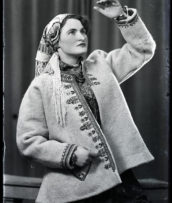 Zdjęcie zrobione w zakładzie fotograficznym. Kobieta ubrana w spódnicę, haftowaną kurtkę (czusze) szczawnicką z chustą na głowie