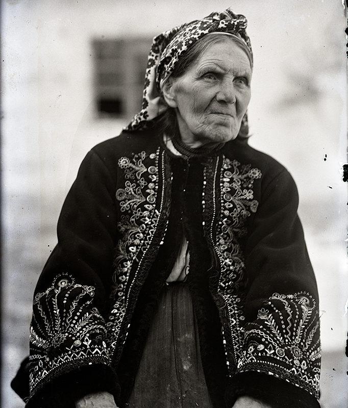 Starsza kobieta w stroju Lachów Sądeckich ubrana w prostą spódnicę, w haftowanym okryciu wierzchnim i w chuście na głowie siedząca na tle domu