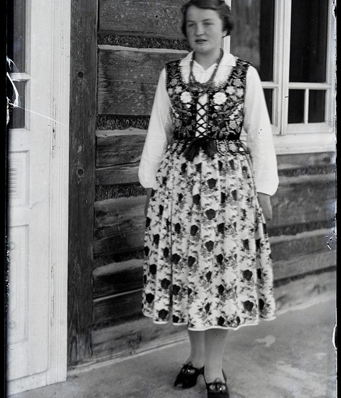 Kobieta w spódnicy w kwiaty, białej bluzce i bogato zdobionym gorsecie na tle drewnianego domu - strój łącki z Kamienicy