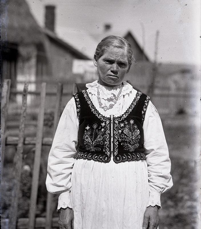 Starsza kobieta w stroju łąckim ubrana w prostą białą koszulę i bluzkę z bogato haftowaną kamizelką. W tle zabudowania gospodarcze