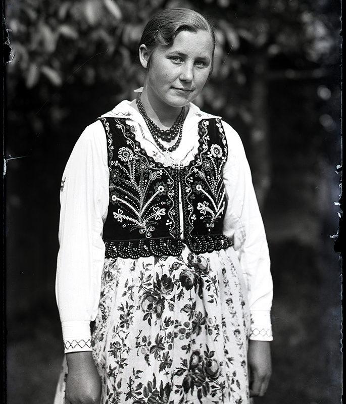 Kobieta w stroju łąckim ubrana w spódnicę w kwiaty, haftowaną lnianą, białą koszulę, bogato haftowany gorset oraz korale