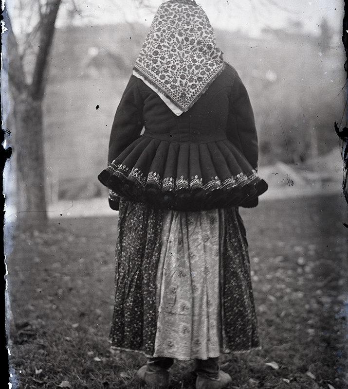 Stojąca tyłem kobieta w spódnicy w kwiaty, w kurtce z baskinką haftowaną u dołu i chustą w kwiatowy wzór na głowie - strój Lachów Sądeckich.