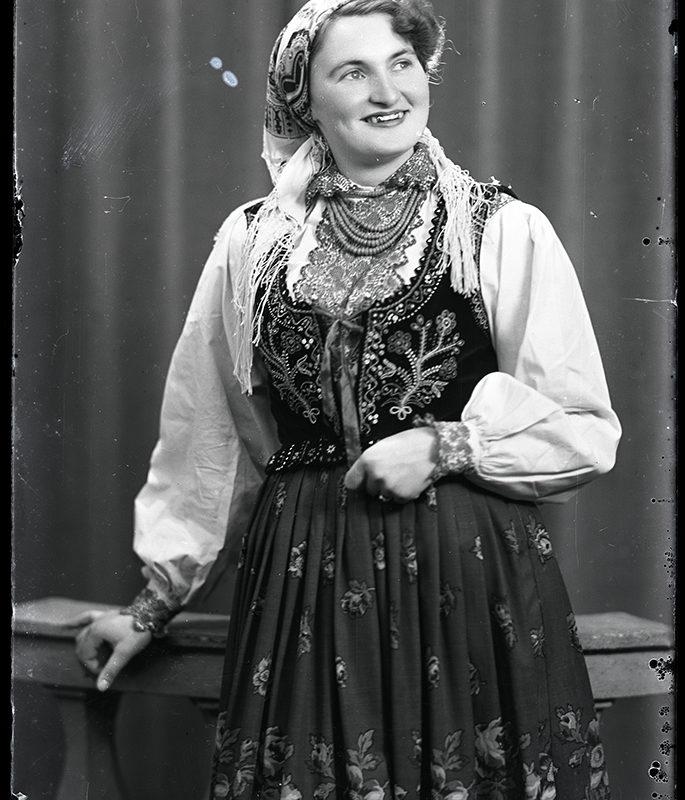 Kobieta w spódnicy w kwiaty, białej haftowanej bluzce i bogato zdobionym gorsecie z koralami i chustą na głowie stojąca w atelier fotograficznym - strój Lachów Sądeckich