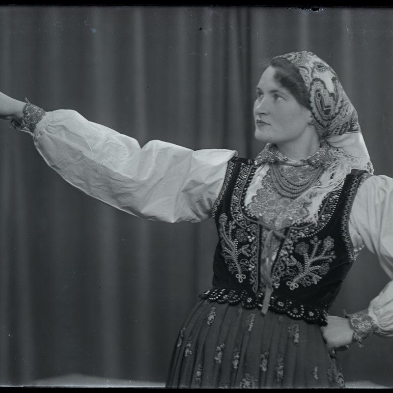 Kobieta w spódnicy w kwiaty, białej haftowanej bluzce i bogato zdobionym gorsecie z koralami i chustą na głowie, stojąca w atelier fotograficznym - strój Lachów Sądeckich