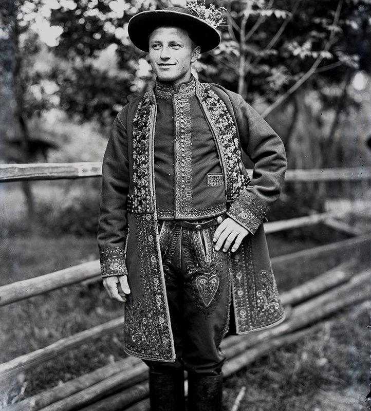 Mężczyzna w kaftanie, pasie, butach karbiakach, koszuli haftowanej z cioskiem i w kapeluszu ozdobionym kwiatami – strój Lachów Sądeckich z Podegrodzia