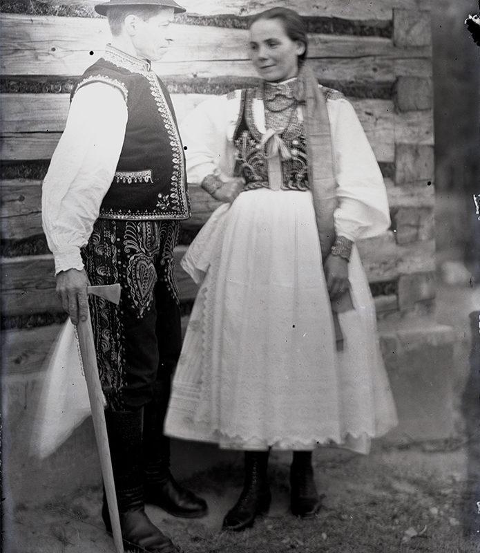 Kobieta i mężczyzna w stroju Lachów Sądeckich stojący na tle drewnianej ściany. Kobieta ubrana w białą spódnicę i fartuch, w białą lnianą koszulę oraz haftowany gorset. Mężczyzna w haftowanych spodniach, białej koszuli, haftowanej kamizelce i w kapeluszu, podpierający się ciupagą.