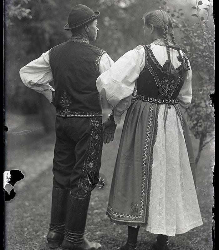 Kobieta i mężczyzna stojący tyłem w stroju Lachów Sądeckich. Kobieta ubrana w spódnicę i fartuch, w białą lnianą koszulę oraz haftowany gorset. Mężczyzna w haftowanych po bokach spodniach, białej koszuli, haftowanej kamizelce i w kapeluszu