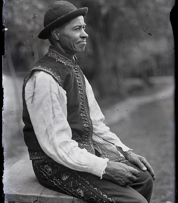 Siedzący bokiem na stołku mężczyzna w ozdobnych spodniach, białej lnianej koszuli, haftowanej kamizelce i w kapeluszu – strój Lachów Sądeckich