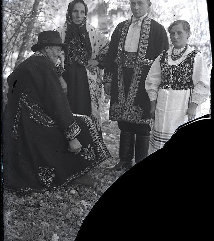 Grupa czterech osób. Starsza kobieta w spódnicy oraz haftowanej kurtce, na ramionach i głowie ma haftowaną chustę, młodsza kobieta w spódnicy, w białej haftowanej bluzce oraz bogato haftowanym gorsecie, z koralami na szyi. Starszy siedzący bokiem mężczyzna w w haftowanym okryciu wierzchnim oraz w kapeluszu, młodszy w spodniach, bogato haftowanym okryciu wierzchnim oraz z szerokim skórzanym pasem – strój Lachów Sądeckich