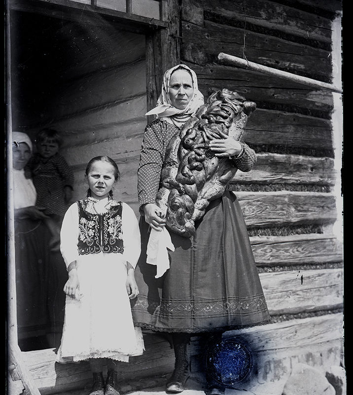 Kobieta w stroju Laszki Sądeckiej z Gostwicy trzymająca chałkę (kukiełkę) wypiekaną na chrzciny, stojąca w progu drewnianej chałupy. Obok dziewczynka w białej haftowanej spódnicy i ozdobnym gorseciku (strój Laszki Sądeckiej).