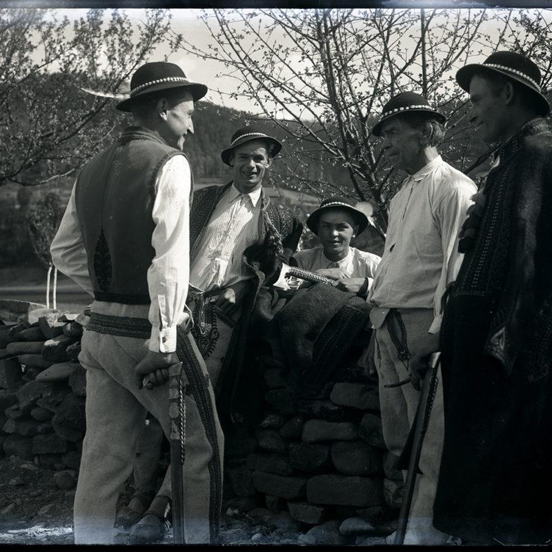 Grupa pięciu mężczyzn w strojach Górali Łąckich z okolic Zarzecza nad Dunajcem opierających się o kamienny murek – w tle sad
