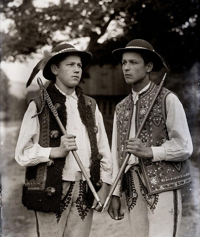 Dwóch mężczyzn w kamizelkach podhalańskich i szczawnickich w kapeluszach zdobionych muszelkami i piórami i trzymających ciupagi