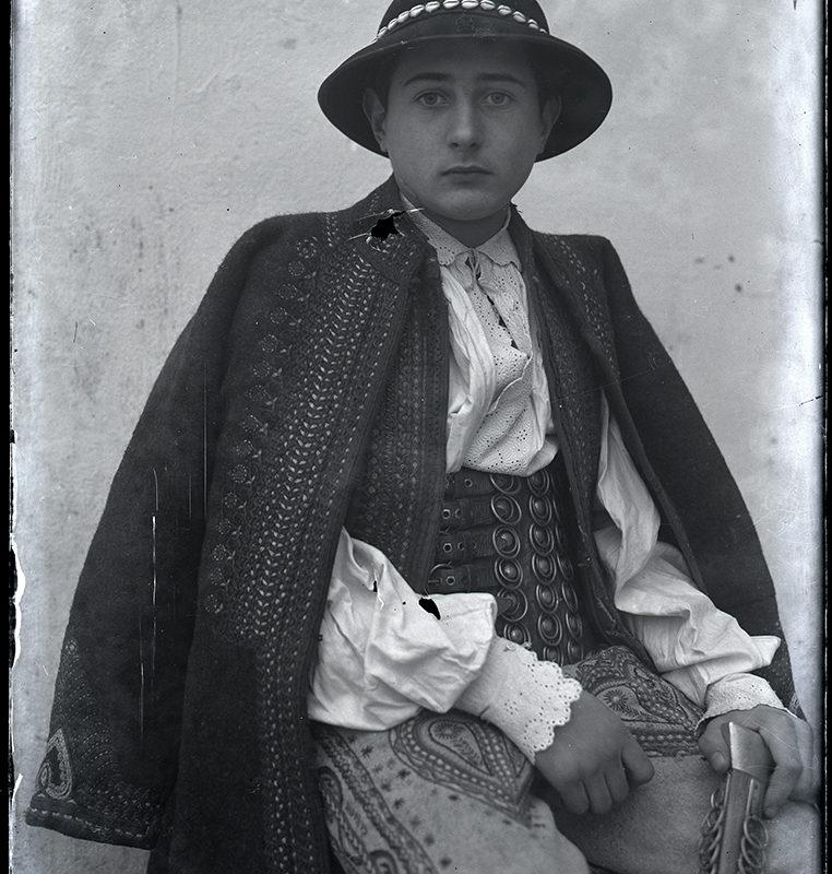 Mężczyzna w zdobionych spodniach, szerokim skórzanym pasie, ozdobnej lnianej koszuli, haftowanej kamizelce i nakryciu wierzchnim oraz kapeluszu przyozdobionym muszelkami, w kierpcach i z ciupagą – strój Górali Łąckich