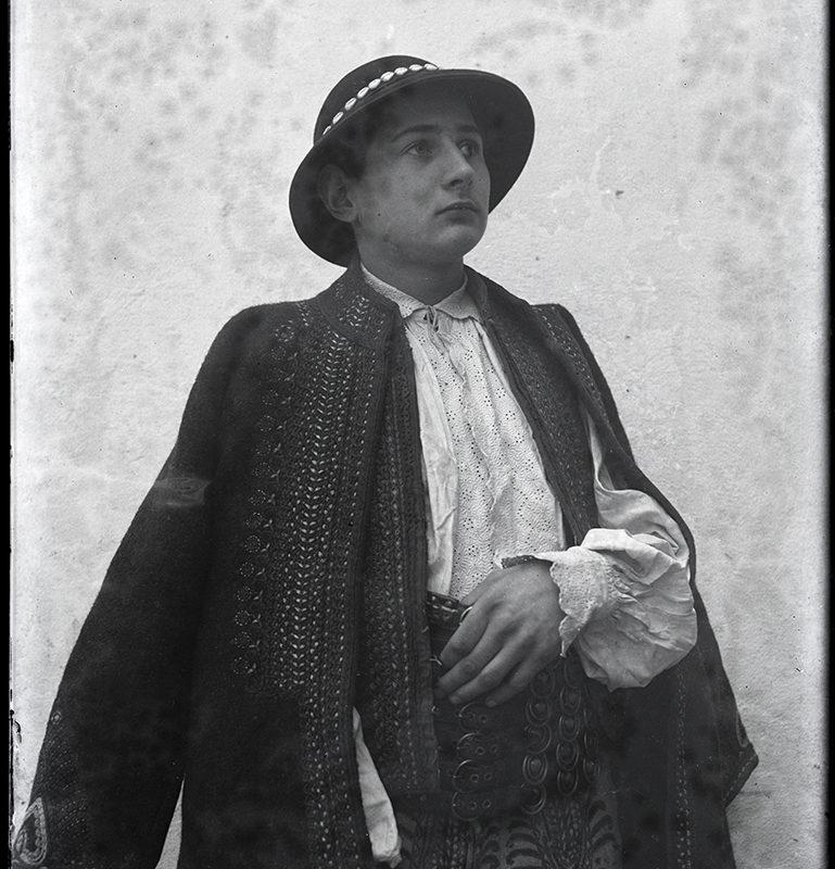 Mężczyzna w zdobionych spodniach, ozdobnej lnianej koszuli, haftowanej kamizelce i nakryciu wierzchnim oraz kapeluszu przyozdobionym muszelkami – strój Górali Łąckich