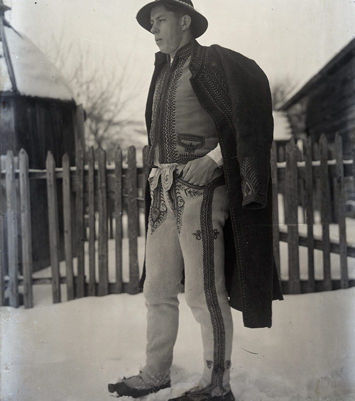 Mężczyzna w stroju górali kamienieckich stojący na podwórzu na śniegu. W tle drewniany płot.
