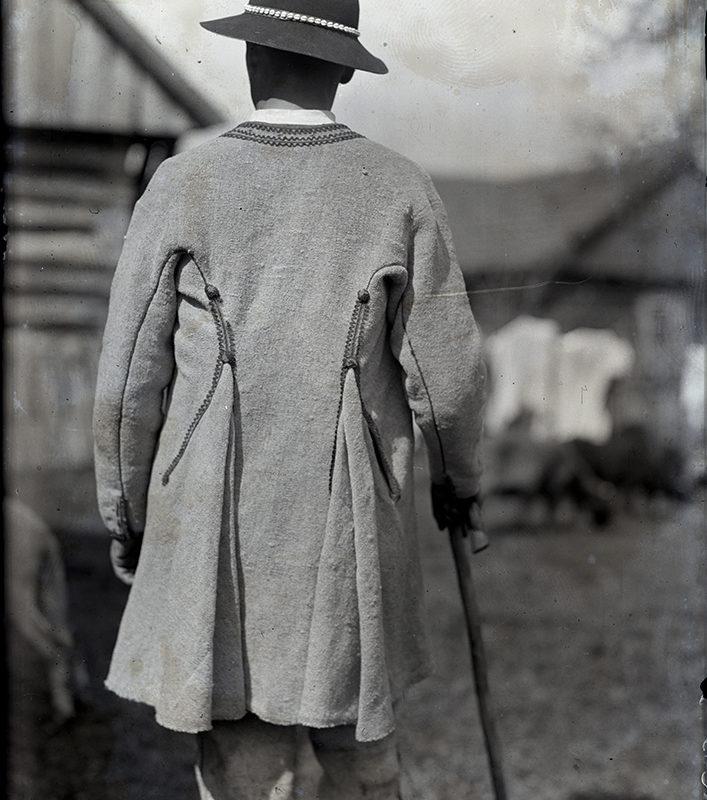 Stojący tyłem mężczyzna w sukmanie górali kamienieckich i kapeluszu zdobionym muszelkami