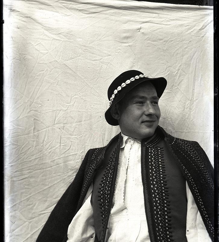 Portret Mieczysława Cholewy w stroju Górali Łąckich, w planie średnim. Mężczyzna patrzy w bok, ubrany jest w kapelusz z deseniem z muszelek, haftowaną sukmanę i białą koszulę. Pozuje na tle białej tkaniny, rozpiętej na drewnianej ścianie budynku.