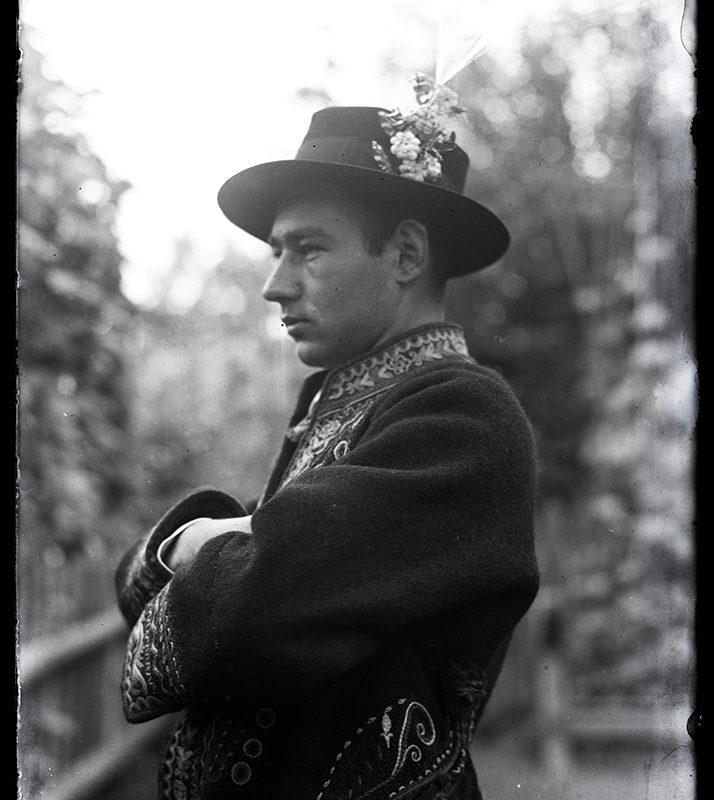 Mężczyzna stojący bokiem w ozdobnym, haftowanym okryciu wierzchnim i w kapeluszu ozdobionym kwiatami – strój Górali Łąckich