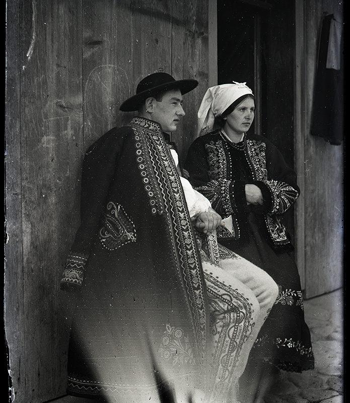 Kobieta w stroju Laszki Sądeckiej w ozdobnej haftowanej spódnicy i bogato haftowanym okryciu wierzchnim w białej chuście na głowie oraz mężczyzna w ozdobnych spodniach i haftowanym okryciu wierzchnim Górali Łąckich – w tle drewniany budynek