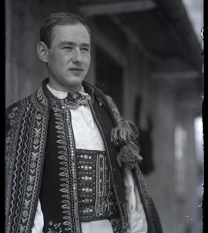 Mężczyzna w białej koszuli, z szerokim skórzanym pasem, ozdobnym haftowanym nakryciu wierzchnim, stojący przed chałupą - strój Górali Łąckich