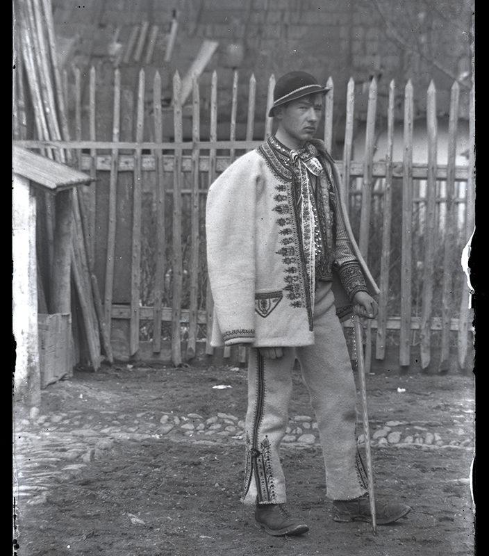 Mężczyzna stojący na podwórzu w ozdobnych spodniach, haftowanej kurtce, kapeluszu zdobionym muszelkami, podpierający się ciupagą – strój Górali Szczawnickich